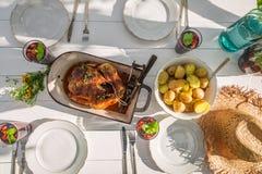 Le dîner fait maison avec des pommes de terre et le poulet ont servi dans le jour ensoleillé Photographie stock libre de droits
