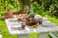Le dîner frais avec des pommes de terre et le poulet ont servi dans le jardin Image libre de droits