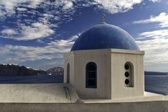 Le dôme grec d'église orthodoxe donne sur la caldeira Images stock
