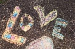 Le ` d'amour de ` de mot écrit dans les craies colorées sur le trottoir Photo stock