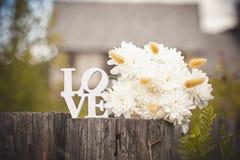 Le ` d'amour de ` de mot fait de lettres en bois blanches, et bouquet des chrysanthèmes blancs Photographie stock libre de droits