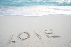 Le ` d'amour de ` de Word sur la plage sablonneuse avec la mousse de mer et la mer ondulent Images stock