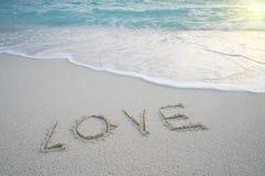 Le ` d'amour de ` de Word sur la plage sablonneuse avec la mousse de mer et la mer ondulent Photos libres de droits