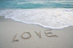 Le ` d'amour de ` de Word sur la plage sablonneuse avec la mousse de mer et la mer ondulent Image stock