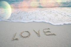 Le ` d'amour de ` de Word sur la plage sablonneuse avec la mousse de mer et la mer ondulent Image libre de droits