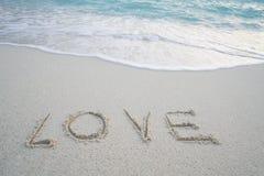Le ` d'amour de ` de Word sur la plage sablonneuse avec la mousse de mer et la mer ondulent Photographie stock libre de droits