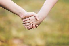 Le ` d'enfants remet se tenir pour l'appui et l'amitié, extérieur avec bleu Image libre de droits