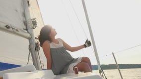 Le damen som kopplar av på däck av segelbåten, solnedgång, sommar arkivfilmer