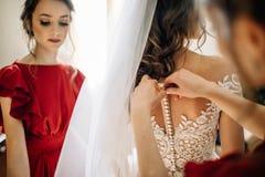 Le damigelle d'onore aiutano la sposa a prepararsi per le nozze immagini stock libere da diritti