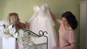 Le damigelle d'onore stanno giocando con un vestito da sposa archivi video