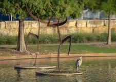 Le ` danse avec le ` en acier par Jerry Daniel et un héron, Hall Park, Frisco, le Texas Photos stock