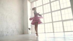 Le danseur du ballet tourne dans la perspective d'une grande fenêtre légère ballerine dans un tutu et un pointe classiques banque de vidéos