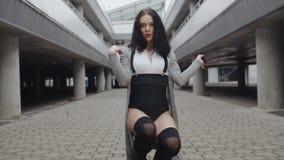 Le danseur féminin exécute la danse moderne de mode, torsion et s'assied, style libre contemporain urbain banque de vidéos