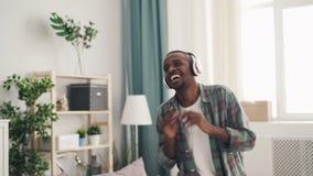Le danseur heureux d'Afro-américain d'homme a l'amusement à la maison écoutant la musique dans les écouteurs et des mains de appl banque de vidéos