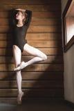 Le danseur mince se tient sur une jambe dans une pose de ballet photo stock