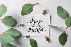 Le ` de citation choisissent d'être ` reconnaissant écrit sur le papier avec des feuilles et des baies sur le fond blanc Vue supé Images stock