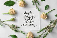 Le ` de citation n'oublient pas d'être ` impressionnant écrit sur le papier avec des roses et des feuilles sur le fond blanc Photo stock