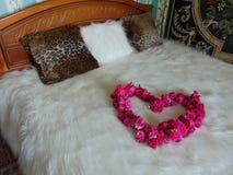 Le ` de coeur de ` des roses sur le lit Images libres de droits