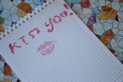 Le ` de ` je t'aime est écrit sur la feuille et la trace du baiser de rouge à lèvres Photographie stock libre de droits