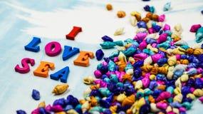 Le ` de mer d'amour du ` I d'expression se compose de lettres en bois colorées sur un fond bleu et blanc et coquilles colorées Image libre de droits