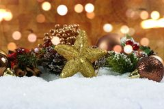 Le decorazioni di Natale e la stella luccicante si sono accoccolate in neve con bok Fotografia Stock