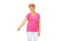 Le den äldre kvinnan som pekar för copyspace eller något Royaltyfri Fotografi