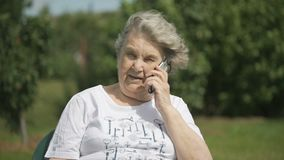 Le den äldre kvinnan som talar genom att använda en smart telefon lager videofilmer