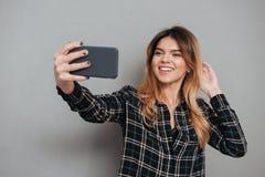 Le den älskvärda flickan som gör en selfie med mobiltelefonen arkivfoton