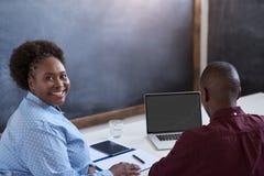 Le den afrikanska affärskvinnan som arbetar med en kollega i ett kontor arkivfoton