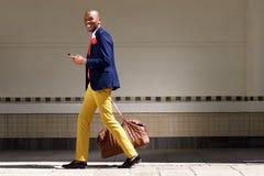 Le den afrikanska affärsmannen som går med påsen och telefonen Arkivfoton