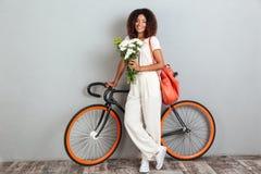 Le den afrikanska kvinnan som poserar med cykeln, ryggsäcken och blommor arkivbild