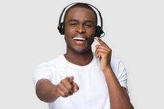 Le den afrikanska mannen i h?rlurar med mikrofon som ser peka fingret p? kameran arkivfoto