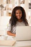 Le den afrikanska tonårs- flickan som hemma använder bärbara datorn royaltyfri bild