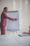 Le den afrikanska unga mannen i exponeringsglas som skriver affärsplan på flipchart Royaltyfri Fotografi
