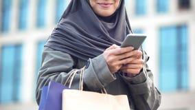Le den arabiska damen som pratar utomhus på telefonen som rymmer shoppingpåsar, grej royaltyfria foton