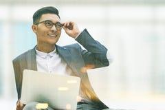 Le den asiatiska affärsmannen med en bärbar dator som tonas Arkivfoto