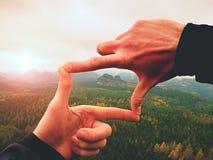 Le den asiatiska affärsmannen som gör en ram med fingrar som isoleras på vit bakgrund arkivfoto