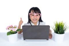 Le den asiatiska kinesiska lilla flickan som använder bärbara datorn med tummar upp Arkivfoto