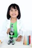 Le den asiatiska kinesiska lilla flickan som arbetar med mikroskopet Royaltyfria Foton