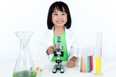 Le den asiatiska kinesiska lilla flickan som arbetar med mikroskopet Royaltyfri Fotografi