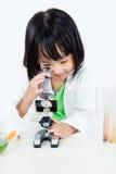 Le den asiatiska kinesiska lilla flickan som arbetar med mikroskopet Arkivbild