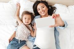 Le den asiatiska kvinnan som tar selfie med hennes lilla dotter royaltyfria foton