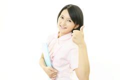 Le den asiatiska kvinnliga sjuksköterskan med tummar upp Arkivbilder