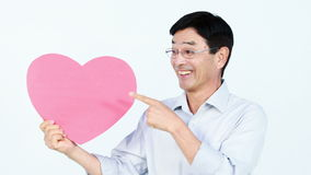 Le den asiatiska mannen som rymmer en rosa hjärta arkivfilmer
