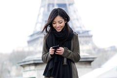 Le den asiatiska unga kvinnan som framme använder hennes mobiltelefon av Eiffeltorn Fotografering för Bildbyråer
