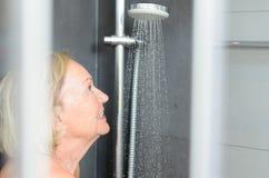 Le den attraktiva höga kvinnan som tar en dusch Arkivbilder