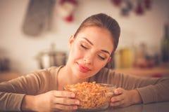 Le den attraktiva kvinnan som har frukosten i kökinre Le attraktiv kvinna Royaltyfri Bild
