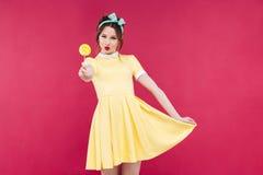 Le den attraktiva utvikningsbrudflickan i söt klubba för gul klänningvisning arkivfoton
