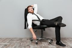 Le den avkopplade affärsmannen som i regeringsställning vilar stol Arkivfoto