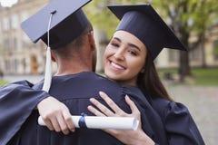 Le den bärande akademikermössan för kandidat som kramar hennes pojkvän Royaltyfri Fotografi